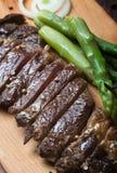 Bifteck de boeuf grillé sur un fond rustique en bois image stock