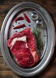 Bifteck de boeuf juteux cru avec le romarin, le sel, le poivre et le poivre de piment d'un plat de fer sur la table en bois images libres de droits