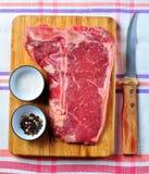 Bifteck de boeuf juteux cru d'à l'os sur un conseil en bois avec du sel, le poivre et un couteau photos stock