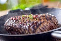 Bifteck de boeuf Bifteck juteux de Rib Eye dans la casserole sur le conseil en bois avec l'herbe et le poivre image stock