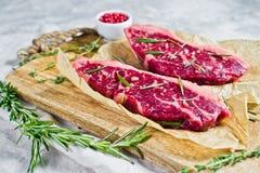 Bifteck de boeuf marbr? cru Angus noir sur un hachoir en bois avec le romarin et le poivre rose Fond gris, vue sup?rieure image stock