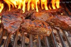Bifteck de boeuf sur le gril de BBQ avec des flammes. Photos libres de droits