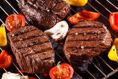 Bifteck de boeuf sur un gril de barbecue avec des légumes Images stock