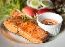 Bifteck de poissons avec de la sauce et le légume à l'arrière-plan photos stock