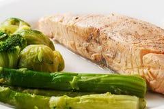 Bifteck de poissons rouge grillé avec les choux et l'asperge de bruxelles dans un plat sur un fond blanc d'isolement images stock