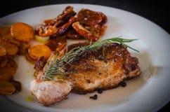 Bifteck de porc avec les carottes rôties et les tomates sèches Photographie stock