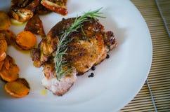 Bifteck de porc avec les carottes rôties et les tomates sèches Photographie stock libre de droits