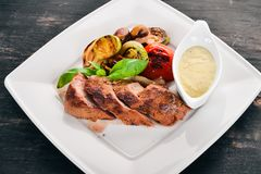 Bifteck de porc avec les légumes grillés d'un plat Image libre de droits