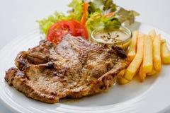 Bifteck de porc avec les pommes frites et la salade sur un fond blanc Photos stock