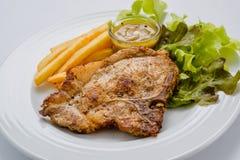 Bifteck de porc avec les pommes frites et la salade sur un fond blanc Image libre de droits