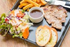 Bifteck de porc dans le plat sur la table Photographie stock