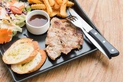 Bifteck de porc dans le plat sur la table Image libre de droits