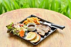 Bifteck de porc dans le plat sur la table Photo stock