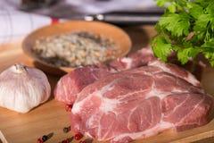 Bifteck de porc sur une planche à découper Photos libres de droits