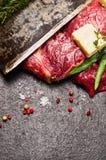 Bifteck de viande crue avec du beurre, les assaisonnements frais et la lame du vieux couteau sur le fond en pierre foncé Photos libres de droits