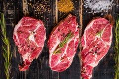 Bifteck de viande crue sur le fond en bois foncé prêt à la torréfaction photographie stock