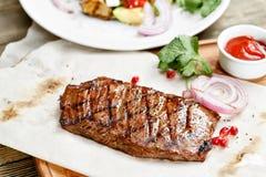 Bifteck du boeuf de marbre, grillé Servir sur un conseil en bois sur une table rustique Menu de rôtisserie, une série de photos Photos stock
