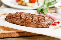 Bifteck du boeuf de marbre, grillé Servir sur un conseil en bois sur une table rustique Menu de rôtisserie, une série de photos Photographie stock