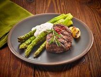 Bifteck et asperge de boeuf grillés de plat foncé photographie stock
