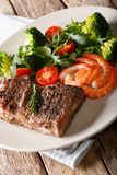 Bifteck et crevettes roses barbequed juteux délicieux avec de la salade végétale image stock