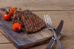 Bifteck et tomates de deux grils sur la planche à découper Photos stock