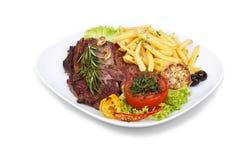 Bifteck grillé avec des pommes frites et des légumes dessus Image libre de droits