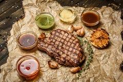 Bifteck grillé avec différentes sauces, sur le parchemin Vue supérieure verticale Image libre de droits