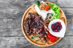 Bifteck grillé de Ribeye sur l'os avec de la sauce à baie, la salade fraîche et les légumes grillés sur la planche à découper sur Photographie stock libre de droits