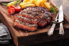 Bifteck grillé rare moyen coupé en tranches Ribeye avec des pommes frites Image libre de droits