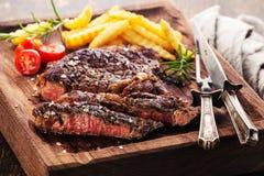 Bifteck grillé rare moyen coupé en tranches Ribeye avec des pommes frites Images stock