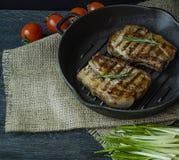 Bifteck grill? sur une casserole ronde de gril, garnie avec des ?pices pour la viande, le romarin, les verts et les l?gumes sur u photos stock