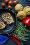 Bifteck grill? sur une casserole ronde de gril, garnie avec des ?pices pour la viande, le romarin, les verts et les l?gumes sur u images stock