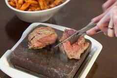 Bifteck grésillant du plat en pierre chaud étant découpé en tranches Image libre de droits