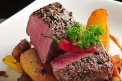 Bifteck juteux avec les pommes de terre et les piments cuits au four photographie stock