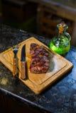 Bifteck moyen juteux de Rib Eye de boeuf sur le conseil en bois avec les ?pices et le sel d'herbes de fourchette et de couteau images libres de droits