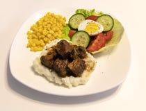 Bifteck, pommes de terre, sauce au jus, maïs et salade images libres de droits