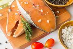 Bifteck saumoné cru saumoné de poisson frais avec le poivre de sel de mer et l'mauvaise herbe d'aneth d'isolement sur un fond bla photo stock