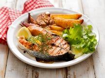Bifteck saumoné grillé, une partie de saumons grillés avec de la laitue fraîche et cales de pomme de terre d'un plat en céramique photos libres de droits