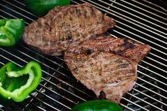 Biftecks avec des poivrons verts sur un gril Photos libres de droits
