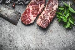 Biftecks crus avec le fendoir de viande et le condiment frais sur le fond concret rustique foncé, vue supérieure, frontière photo stock