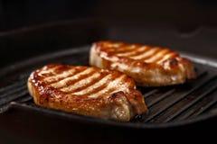Biftecks dans une casserole de fonte Photographie stock