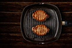 Biftecks dans une casserole de fonte Images libres de droits