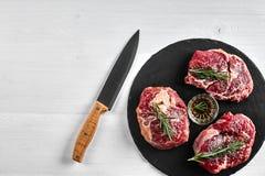 Biftecks de boeuf crus frais avec les herbes, l'ail, l'huile d'olive, le poivre, le sel et le romarin sur le conseil noir : Filet Photographie stock libre de droits