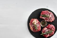 Biftecks de boeuf crus frais avec les herbes, l'ail, l'huile d'olive, le poivre, le sel et le romarin sur le conseil noir : Filet Photos libres de droits