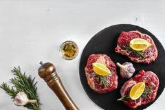 Biftecks de boeuf crus frais avec les herbes, l'ail, l'huile d'olive, le poivre, le sel et le romarin sur le conseil noir : Filet Images stock