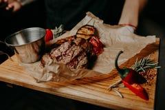 Biftecks de boeuf grillés avec des épices sur la planche à découper en bois Image stock