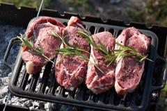 Biftecks de boeuf juteux crus faisant cuire sur le gril dehors photo libre de droits