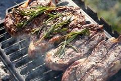 Biftecks de boeuf juteux faisant cuire sur le gril dehors photographie stock libre de droits