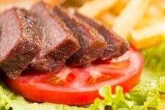 Biftecks de boeuf, pommes frites grillées et légumes en gros plan Image stock