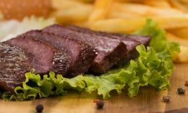 Biftecks de boeuf, pommes frites grillées et légumes en gros plan Images libres de droits